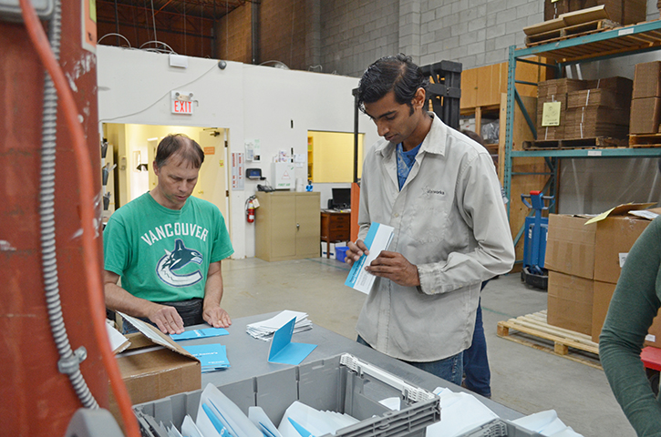 Starworks employees sealing letters in a warehouse